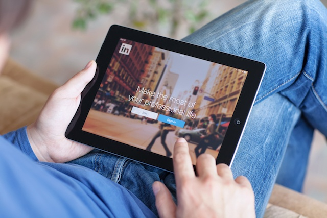 Man holding iPad With LinkedIn on the Screen