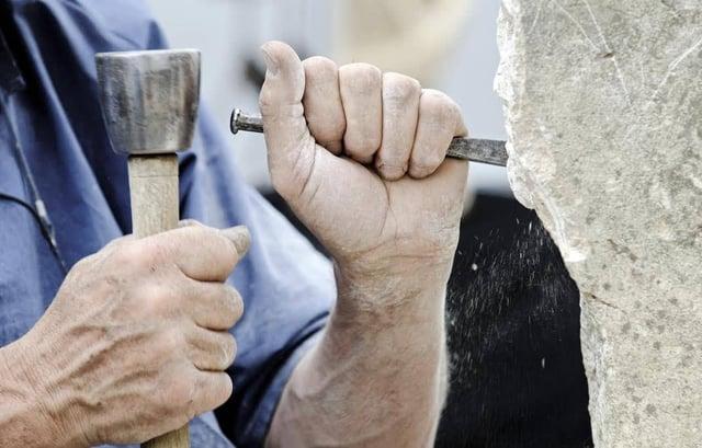 Man hammering a rock